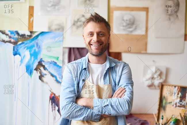 Waist-up portrait of middle-aged bearded art teacher standing against paintings in studio, looking at camera and smiling cheerfully