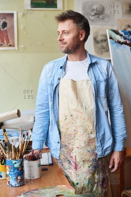 At art class. Dreamy middle-aged painter in stained apron standing in art studio, holding box of pencils and looking to the side