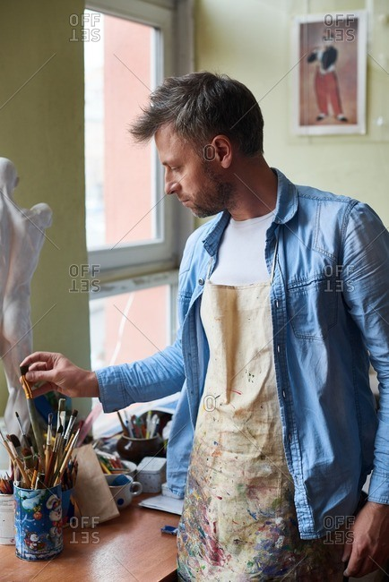 Working in art studio. Pensive middle-aged male artist in stained apron picking perfect paintbrush for creating masterpiece