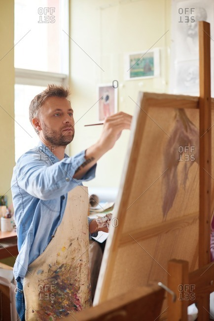 Painting process. Middle-aged fair bearded artist in denim shirt and stained apron standing in front of easel and painting a picture with enthusiasm
