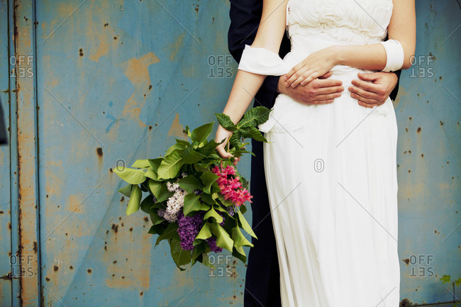 groom hugs his bride, medium close-up