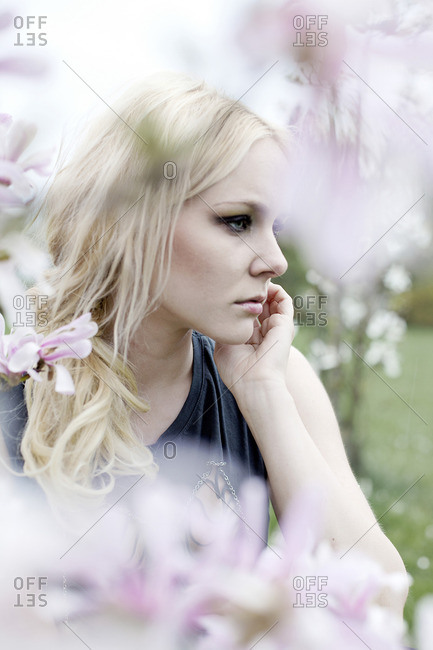 young woman surrounded by blossoms lost in thoughts