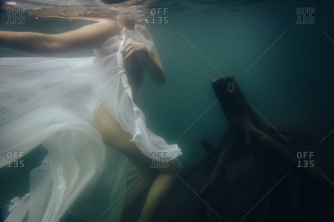Woman is diving under water with cloth