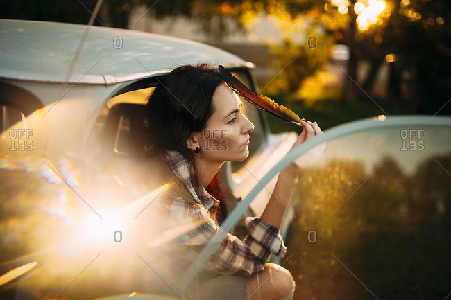 Woman is sitting with feather in the car and peering into distance
