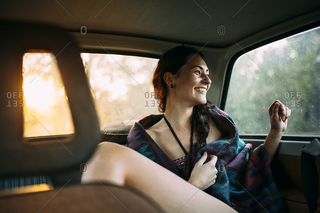 Woman is sitting in car and is laughing out of the window