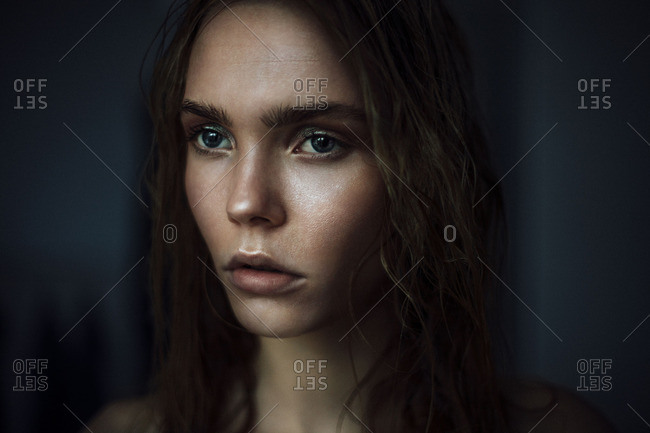young woman looks with wet hairs from the window
