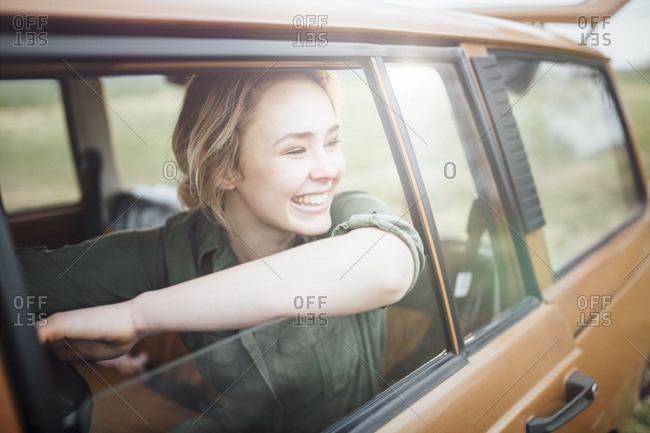 Woman leaning out of a car window and smiles
