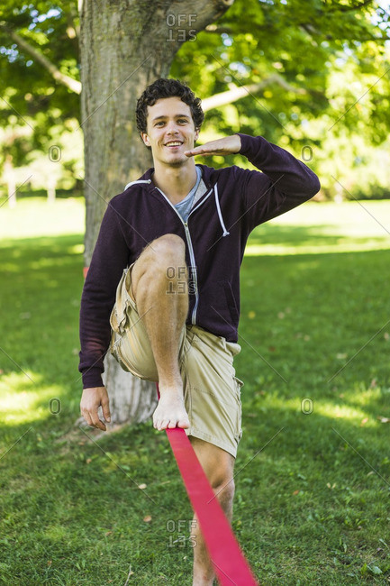 Athletic man attempting to slackline in park, Montreal, Quebec, Canada