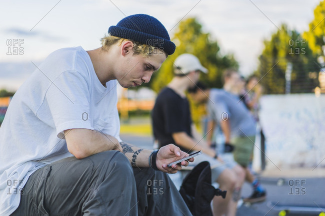 Young skater in skatepark using his smartphone during summer, Montreal, Quebec, Canada