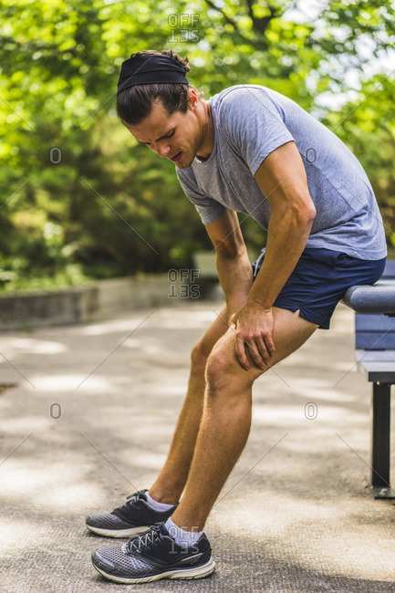 Athletic man with muscle pain in park, Montreal, Quebec, Canada