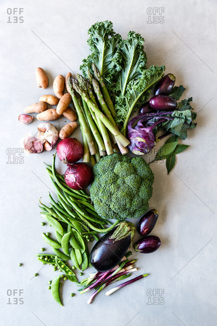 Purple and green vegetables arranged on kitchen table