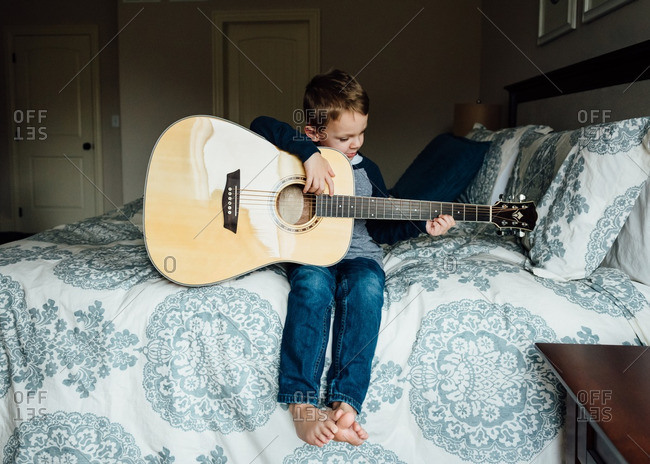 Little boy holding guitar on bed