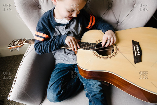 Boy in armchair playing with guitar