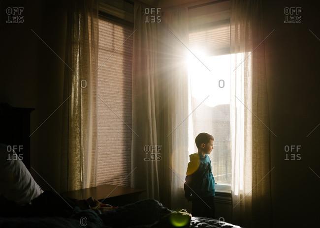 Boy at window in sun flare