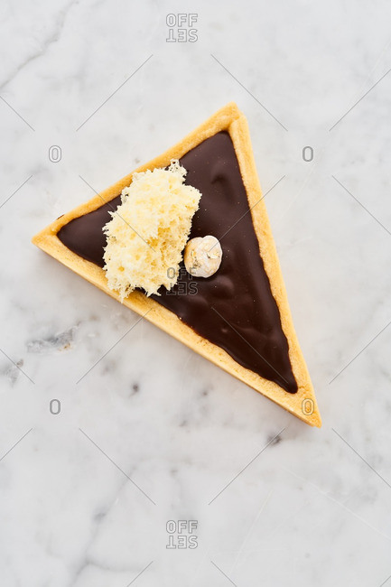 A triangle shaped cake topped with chocolate
