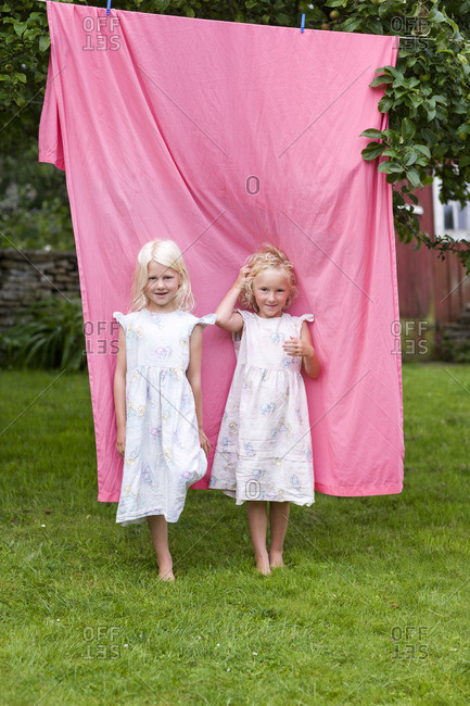 two blonde girls standing in front of laundry in back yard