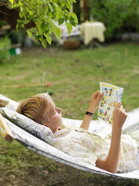 Teenage boy lying down on hammock and reading magazine