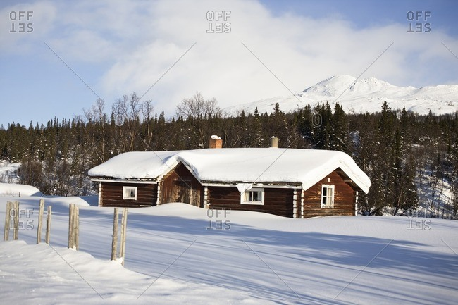 Cottage house covered by fresh snow