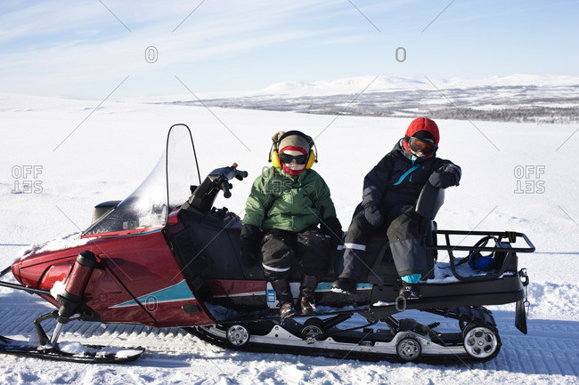 Two boys sitting on snowmobile
