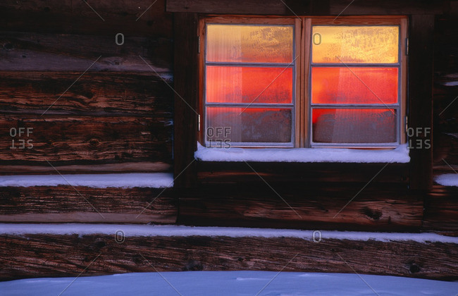 Warm light in log cabin window
