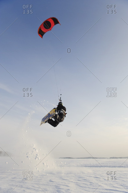 Man jumping in mid air while kite boarding in snow