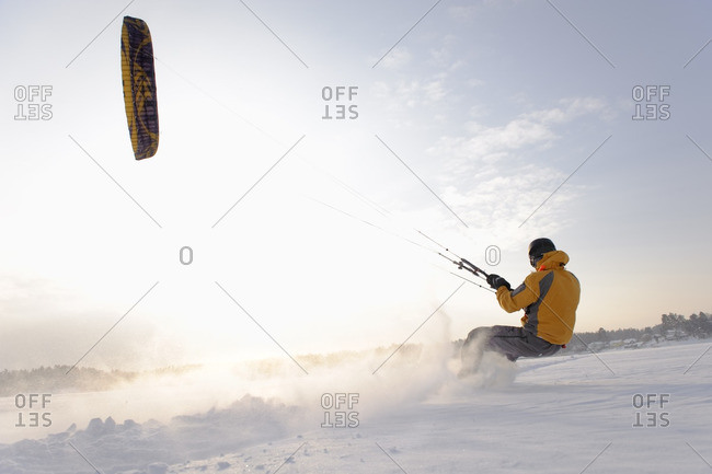 Man kite boarding in snow