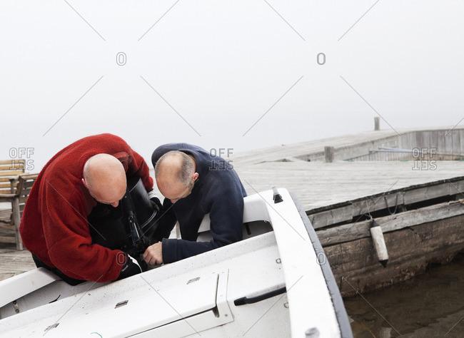 Pair of mature men fixing motorboat