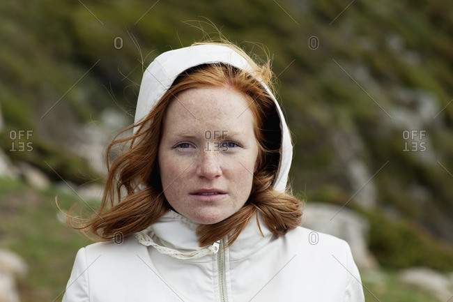 Young redhead woman in hooded shirt looking at camera