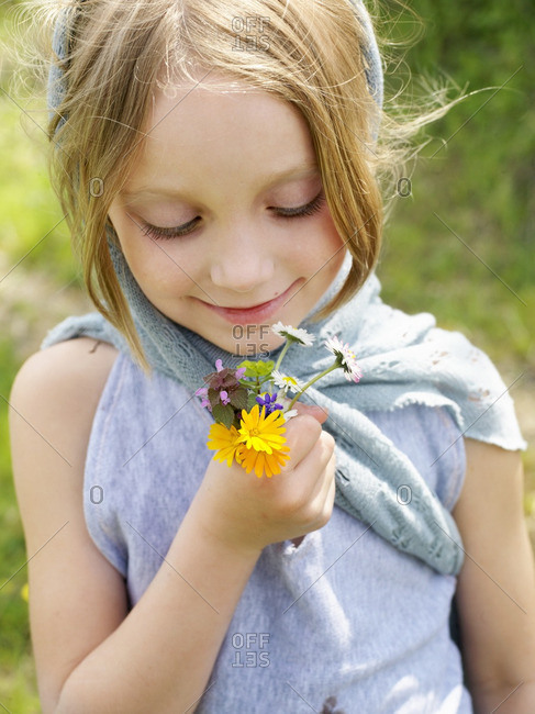 Girl holding bunch of wild flowers