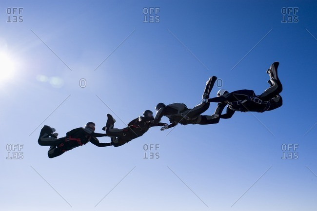 Four people holding hands and flying