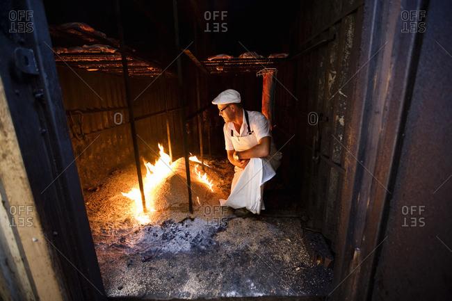 Butcher preparing fire to smoke meat