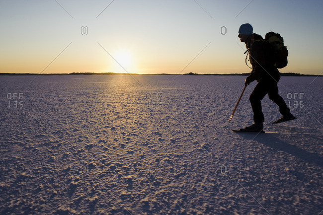 Man ice skating on snow covered landscape at dusk