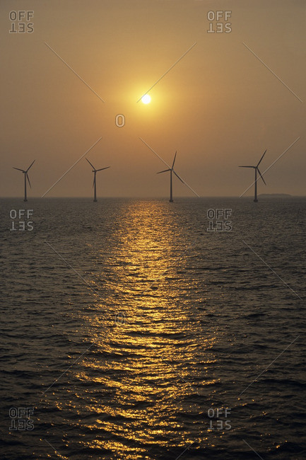 Sea with row of wind turbines in background