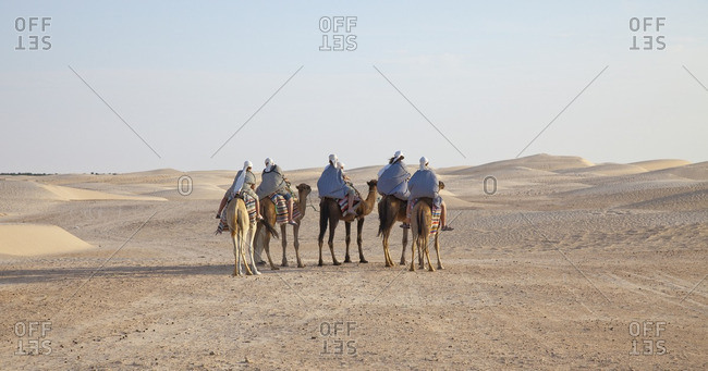 Group of people on camels in desert