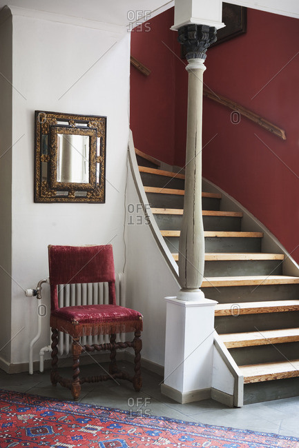 Chair and column beside wooden staircase