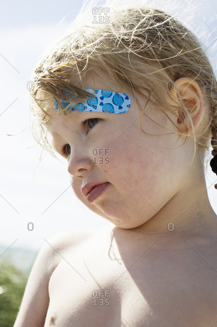 Girl with bandage on forehead, close-up