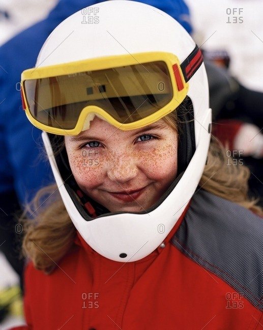 Girl wearing skiwear and goggles smiling, portrait
