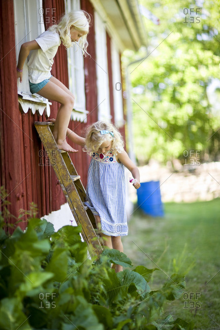 Two girls moving down through ladder from window