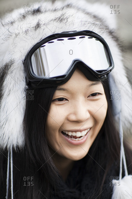 Portrait of happy young woman wearing fur hat and ski goggles