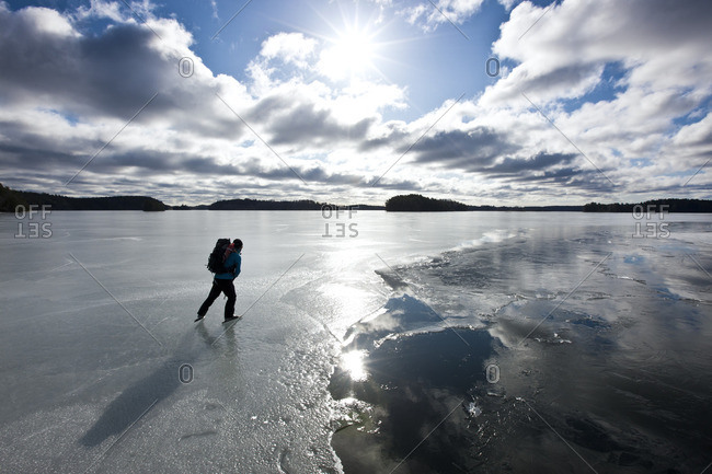 Person ice skating on frozen lake