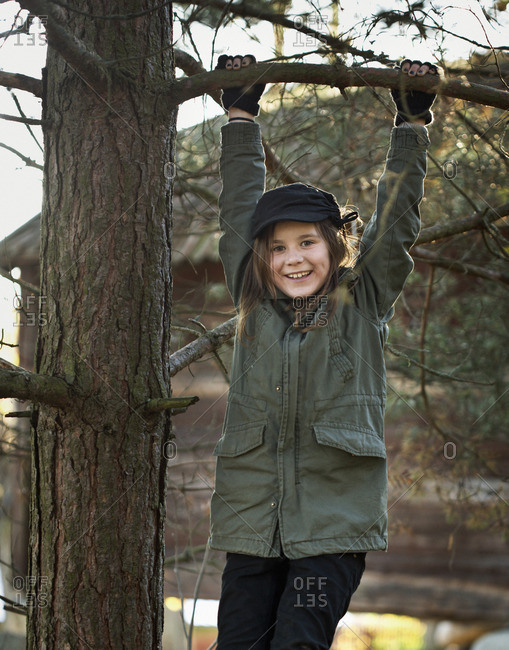 Portrait of girl holding on to tree branch