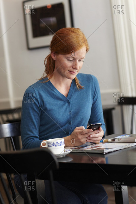 Portrait of young smiling woman in cafe sending message