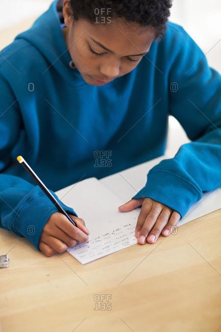 Boy doing notes in school