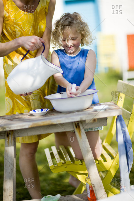 Mother and daughter washing hands in backyard