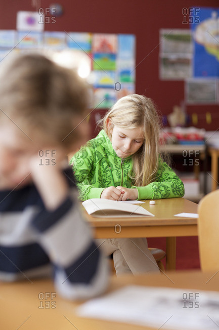 Schoolgirl writing in notebook at classroom