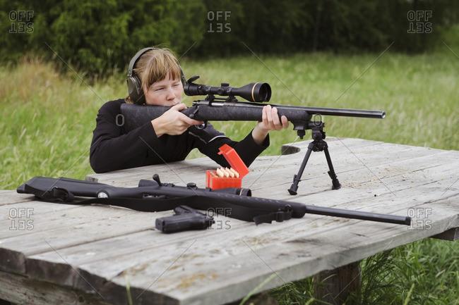Woman target shooting in meadow