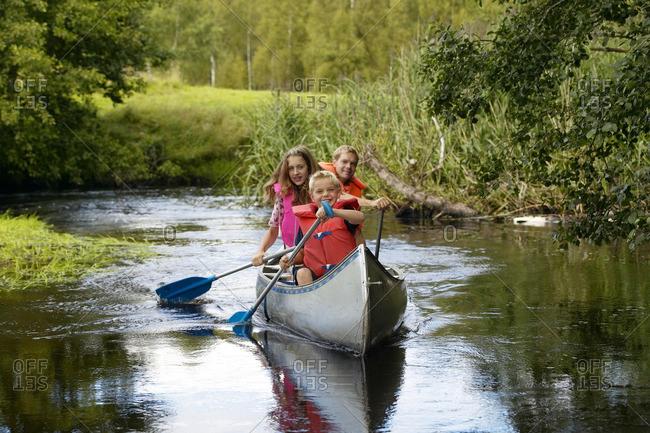 Family canoeing on river