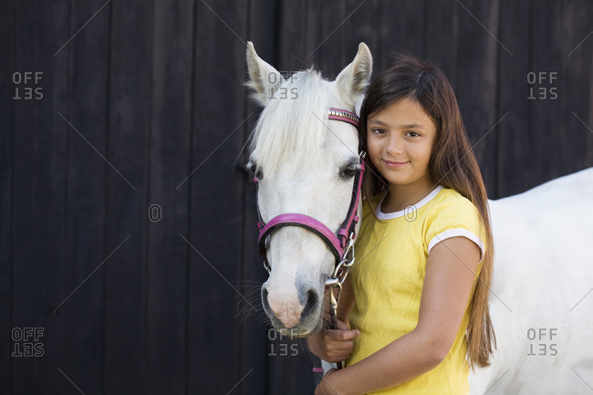 Portrait of girl with white horse