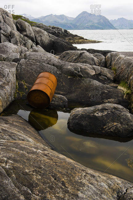 Rusty oil drum on rocky coastline