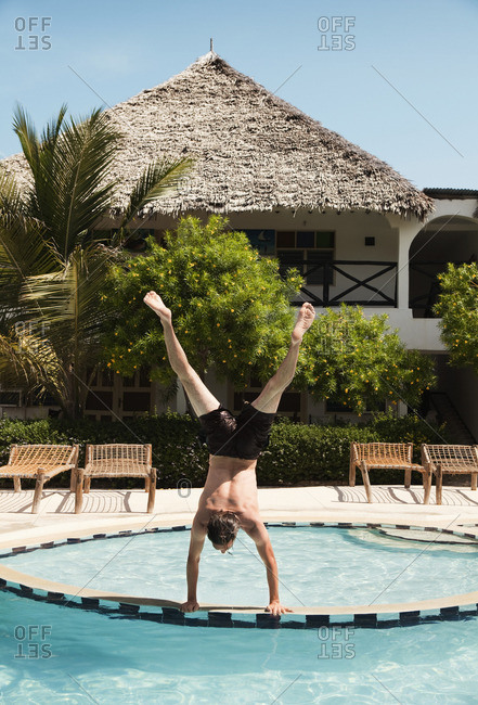 Man doing handstand at poolside